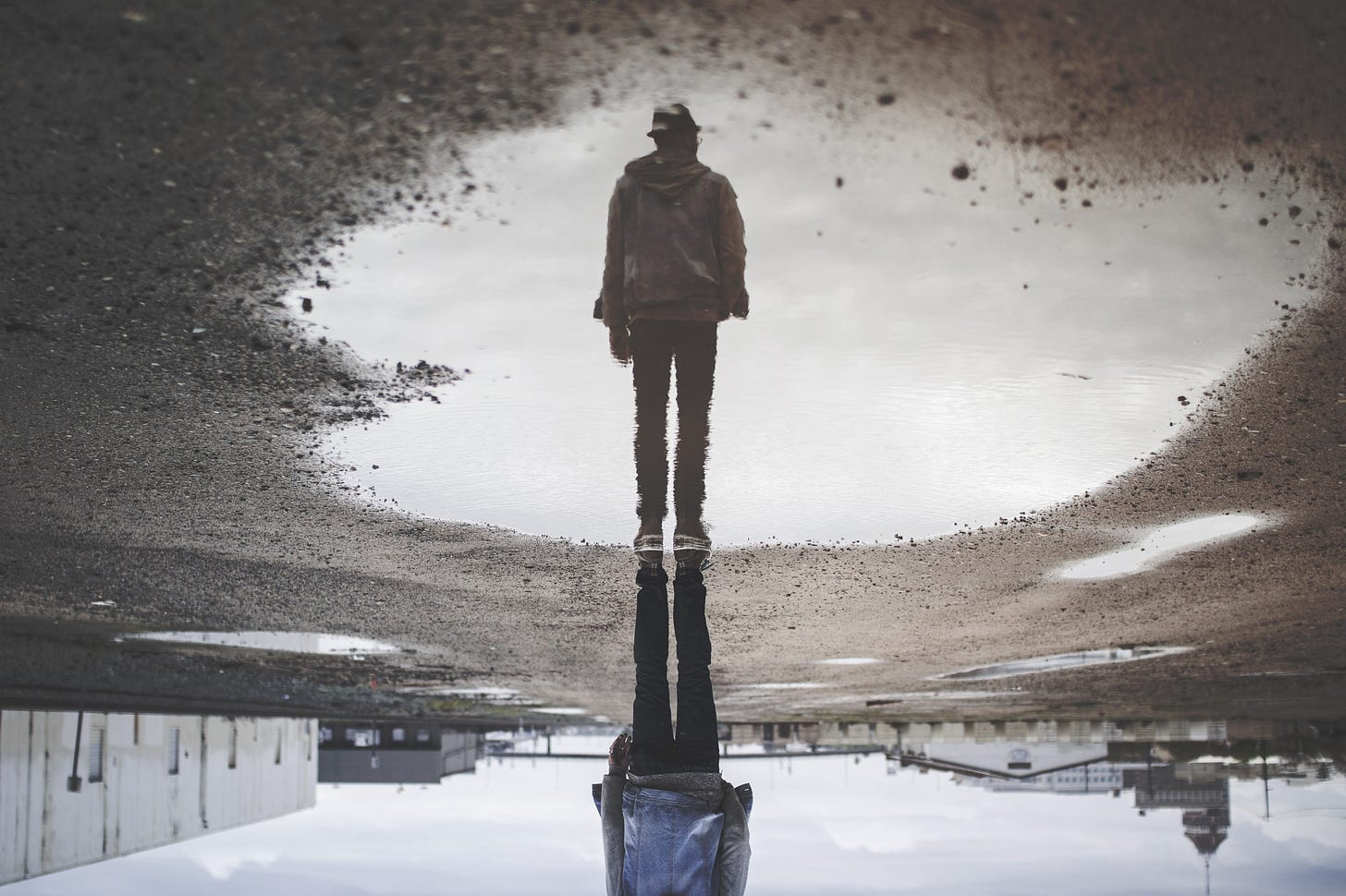 Image of a man's reflection in a puddle for article by Larry G. Maguire
