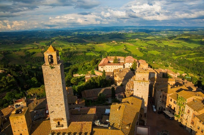 A medieval hill town in the Tuscany region of Italy, tall buildings and countryside stretching out into the horizon