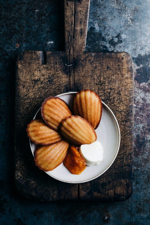 Madeleines with apricot jam and sour cream on a plate, on top of a rustic cutting board.