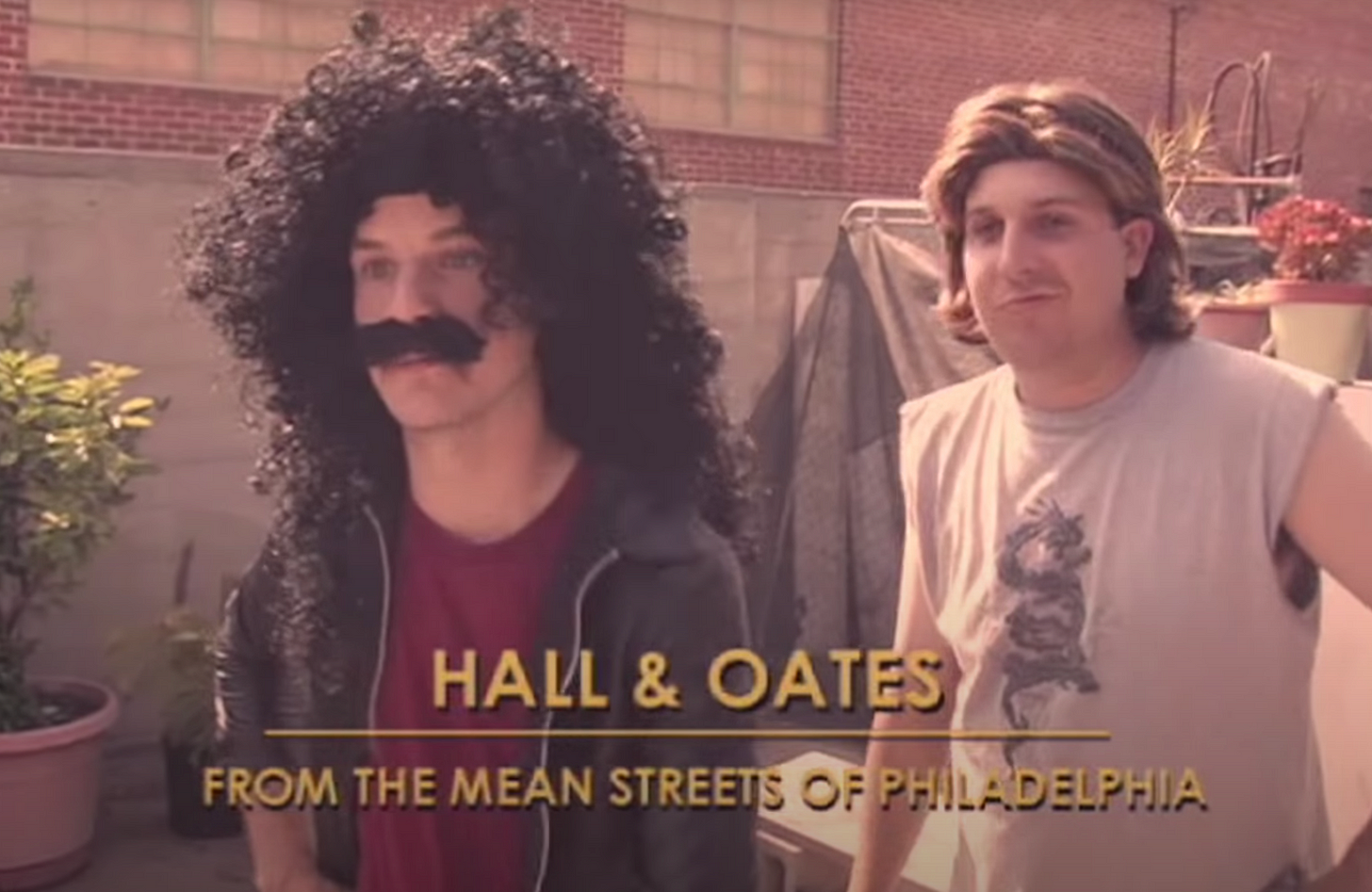 """man in a long black curly wig with a fake moustace. Behind him is a man with a blonde wig. The caption reads """"Hall and Oates - from the mean streets of Philadelphia"""""""