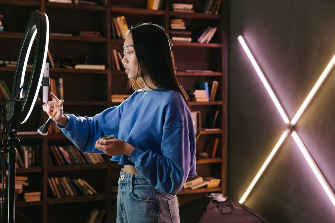 Woman in Blue Long Sleeve Shirt and Blue Denim Jeans Standing Beside Brown Wooden Shelf
