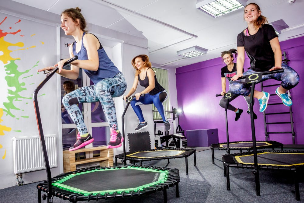 Group of women happily exercising on hexagonal trampolines with stability bars