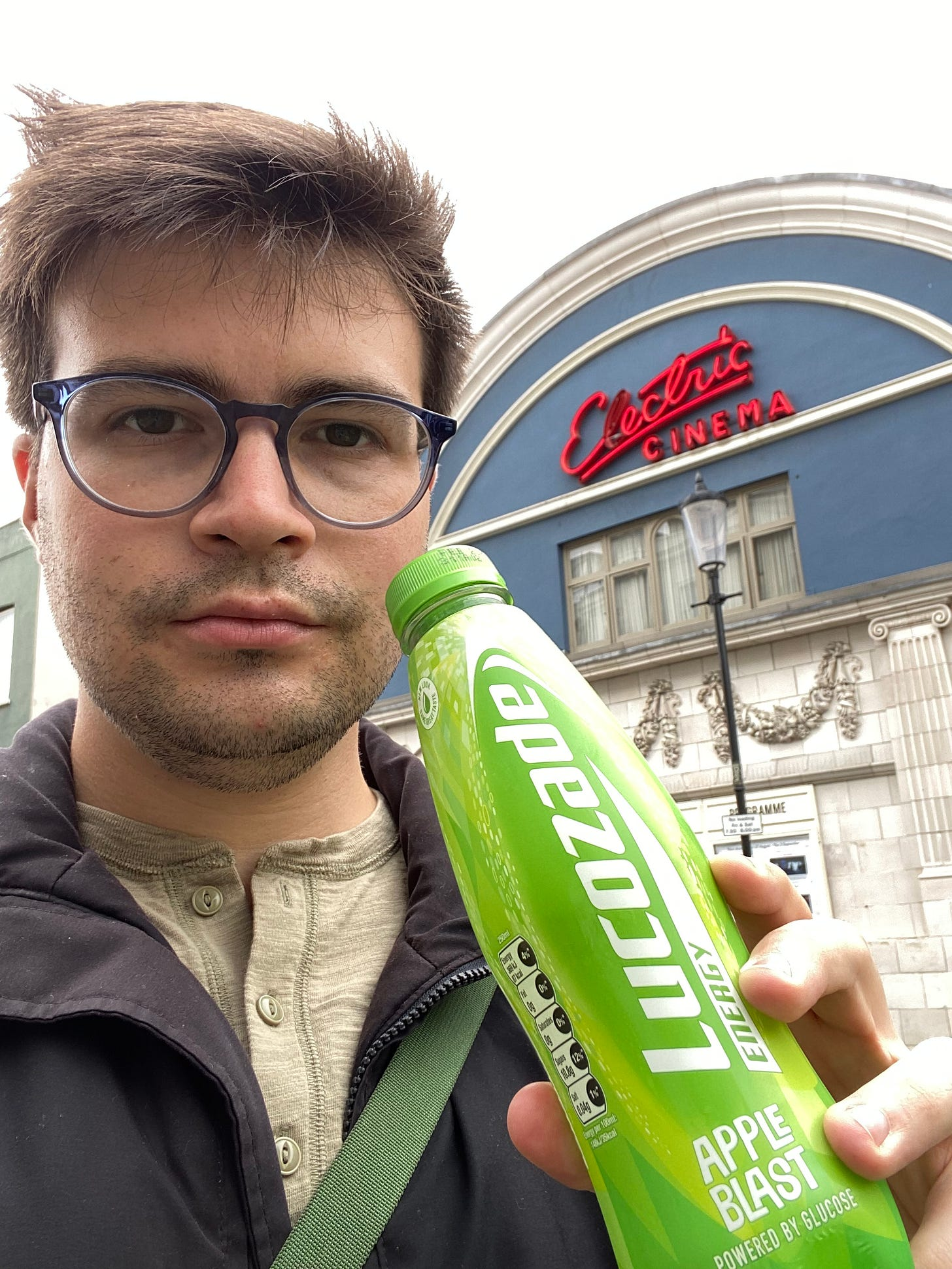 The author standing with a Lucozade Apple Blast in front of Electric Cinema, a movie theater in Notting Hill.