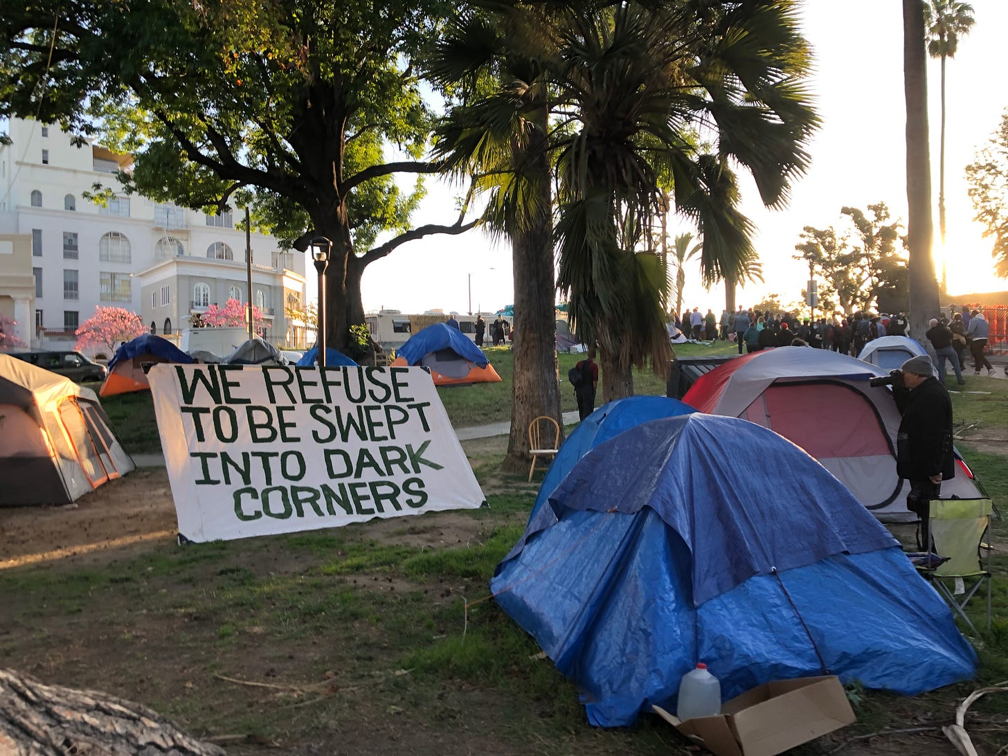 """Tents in the park, and a sign that reads """"WE REFUSE TO BE SWEPT INTO DARK CORNERS"""""""