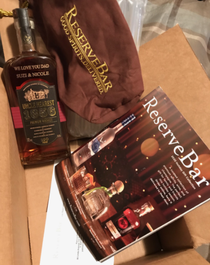 "Image of a bottle of Uncle Nearest whiskey that is engraved with the text, ""We love you dad"" on one line then, ""Suzi & Nicole"" on the next line. There is a cloth bag and a catalog from Reserve Bar, the site the product shipped from."