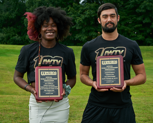 Trish Adora and Wheeler YUTA pose with world title recognition plaques from PWI