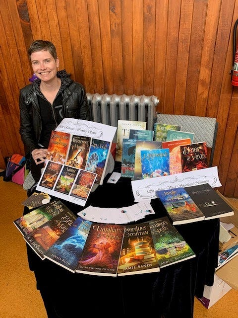 Image contains a woman with short hair and a black jacket sitting to the left of a round table covered with books. Many of the books included are the Witchy Fiction novellas.