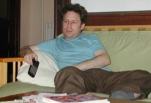 Man sitting on a couch, holding a TV remote