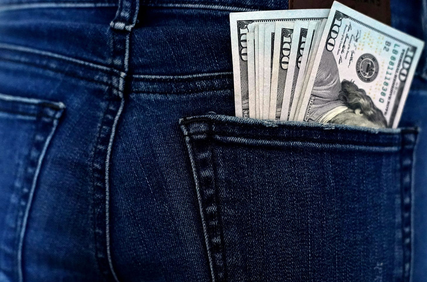 Person wearing blue jeans with hundred dollar bills in their back pocket