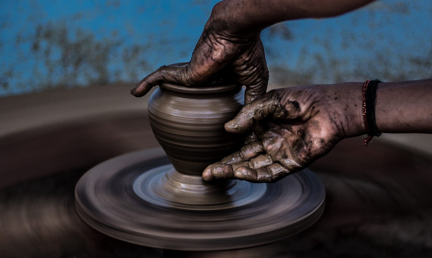 """image of hands forming a clay pot for article titled """"what is an artist"""" by Larry G. Maguire"""