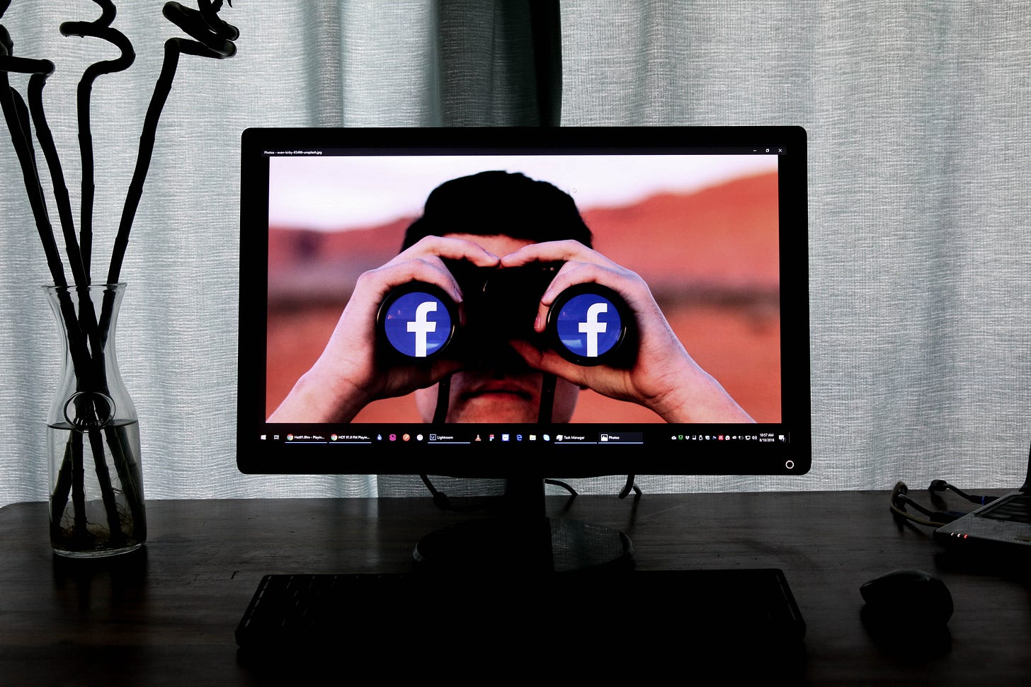 Photo of a computer on a desk showing a photo of a man viewing binoculars with Facebook logos on the outer lenses. Glen Carrie / Unsplash