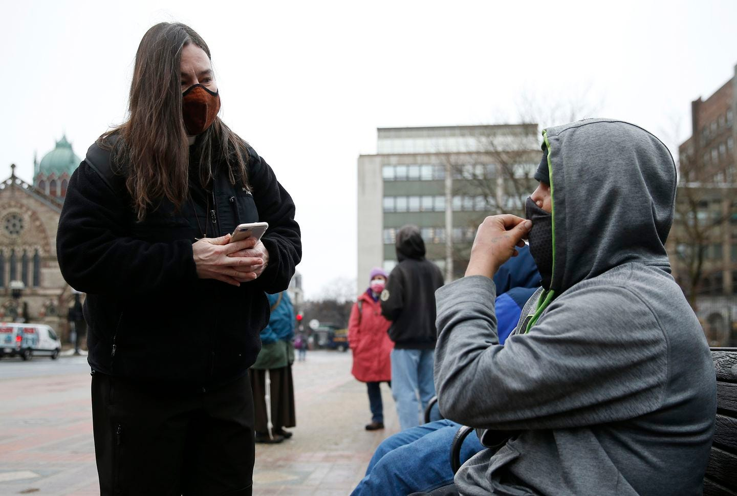 Boston, MA -- 3/1/21 -- Lisa Loughlin, a chaplain who is part of 'Common Cathedral' an organization which has ecumenical services on Boston Common, offers her phone to a homeless man in Copley Square who had asked to use it so he could try and call a family member.  (Jessica Rinaldi/Globe Staff)
