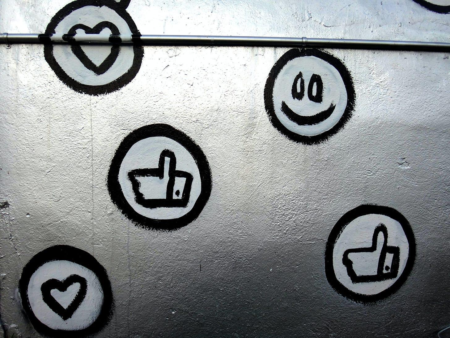 Photo of Facebook reaction emoji painted onto a wall. George Pagan III / Unsplash