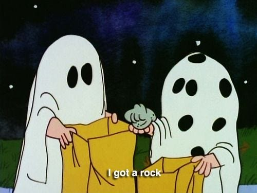 """Two children from A Charlie Brown Halloween dressed as ghosts, with the text """"I got a rock"""""""