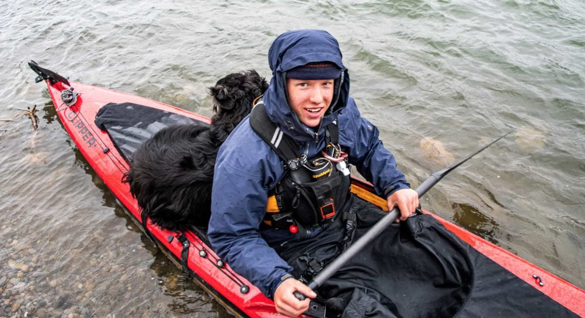 zev heuer paddles his canoe with his dog