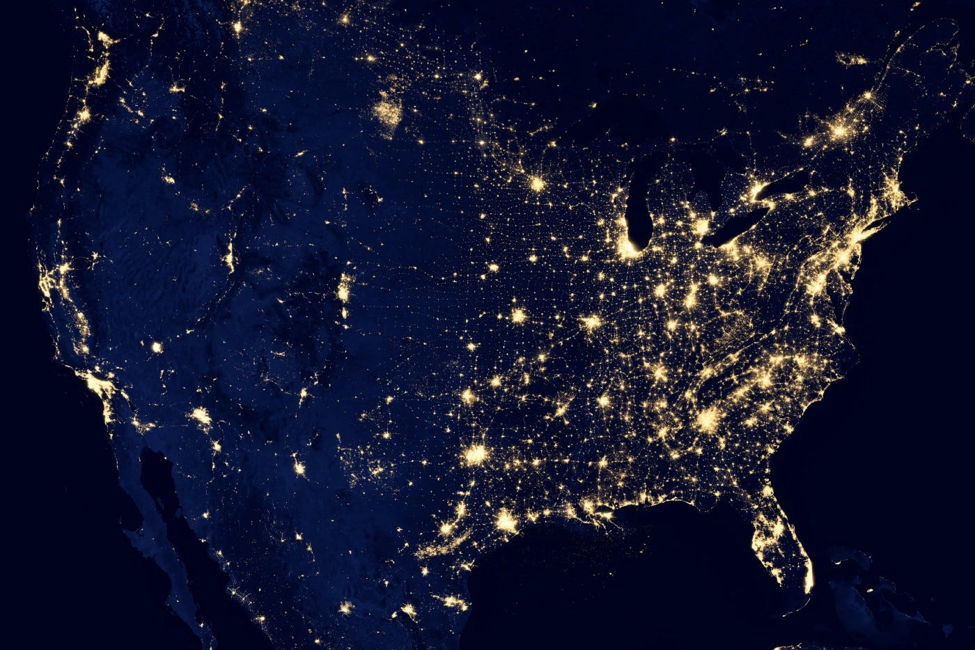 A map of the US at night from space. The east side is filled with lights while the west side is less lit up with the exception of the West coast.
