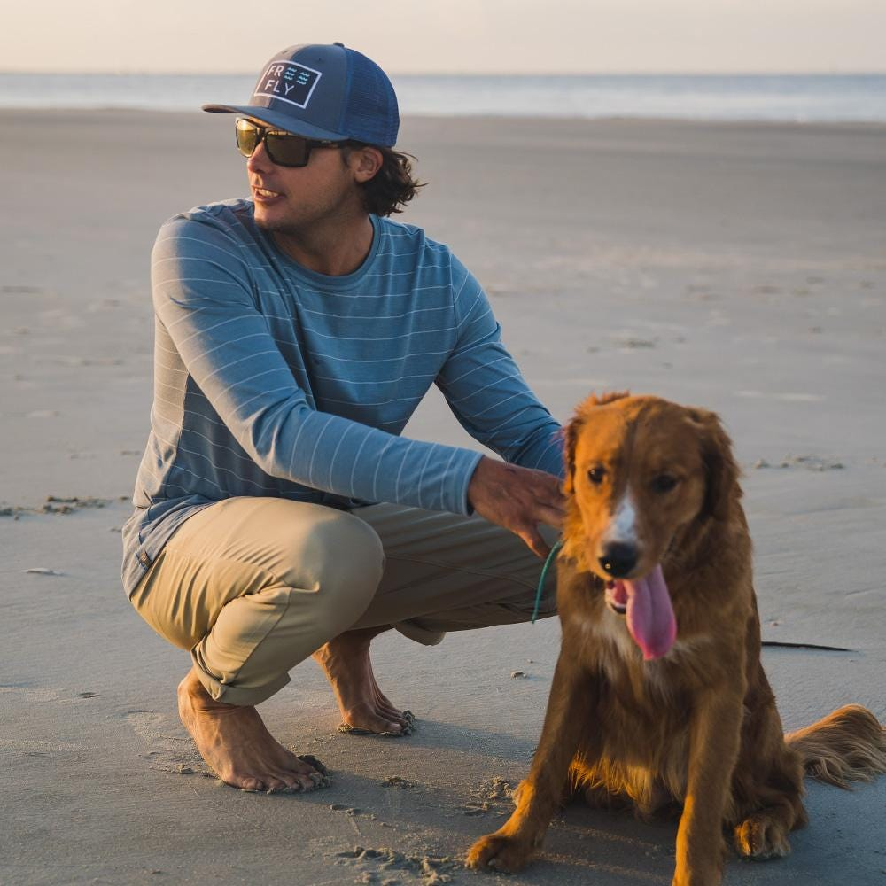 a man wears the free fly bamboo shoreline shirt on the beach while petting his dog