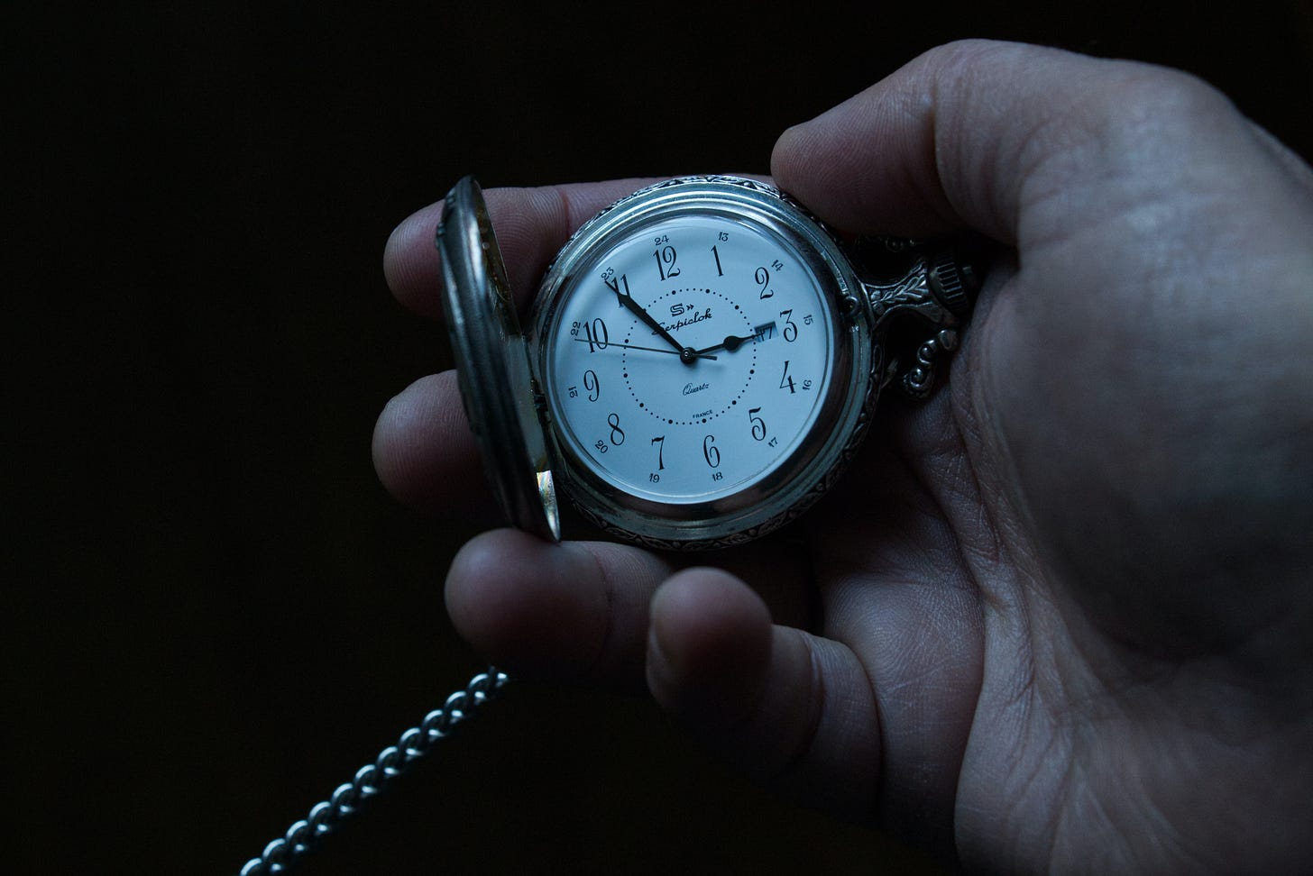 person holding pocketwatch with time visible