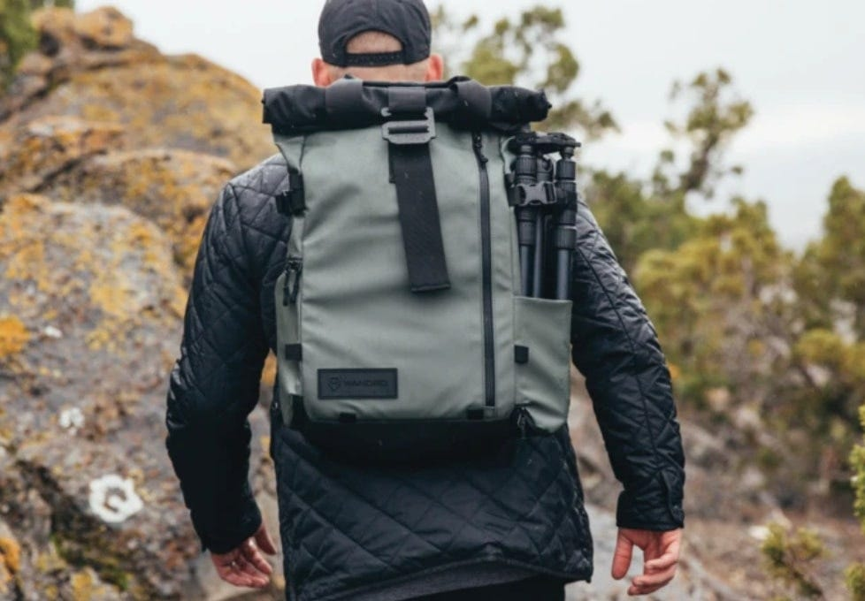 a man wearing the PRVKE pack hikes up a hill to take an epic picture at the top