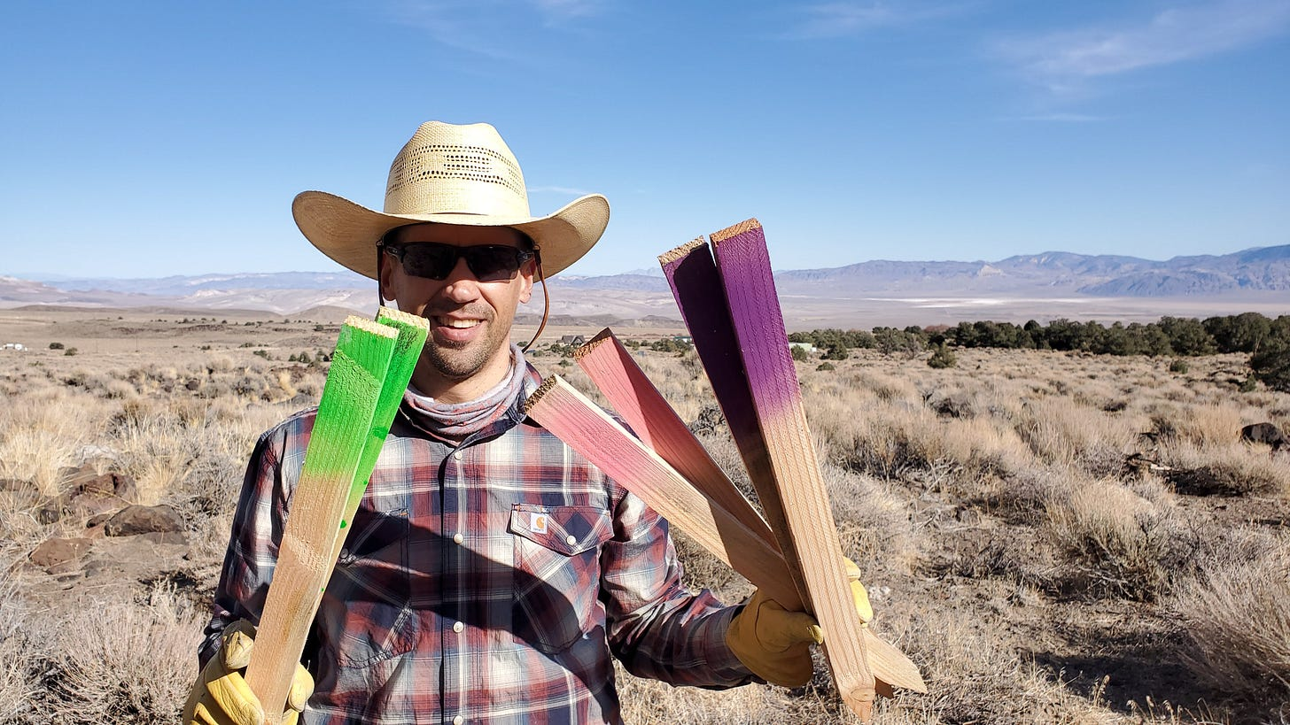 Eric holding wooden stakes with spray painted ends in green and purple for staking out the ground.