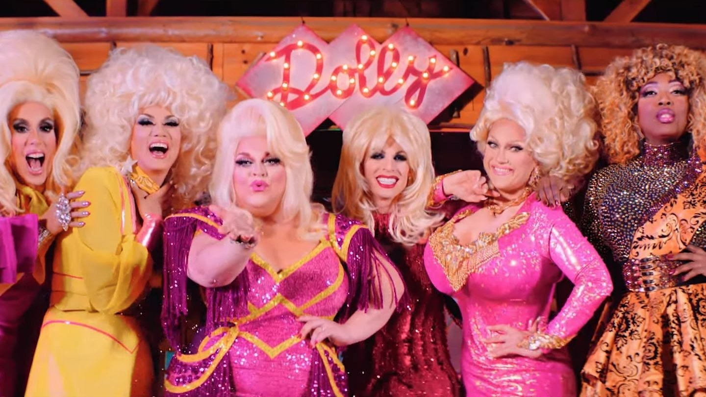 """Photo of six drag queens dressed in pink and yellow sequin gowns with blonde wigs. They are standing in front of a pink sign that reads """"Dolly"""" in cursive with lights."""