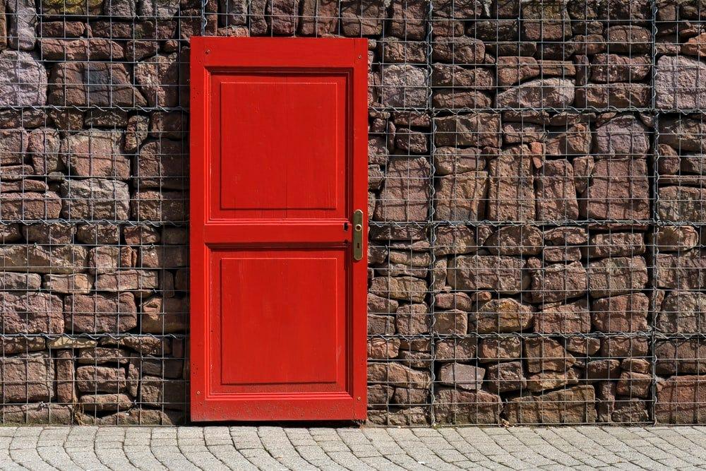 red 2-panel door on black metal chain link board
