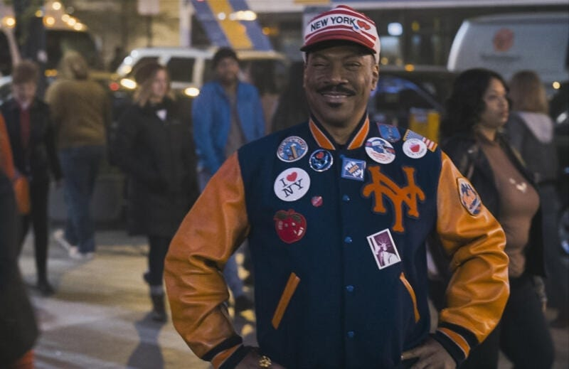 Eddie Murphy as King Akeem in 'Coming 2 America', smiling towards the camera, in the middle of a street crowd, wearing New York iconography.