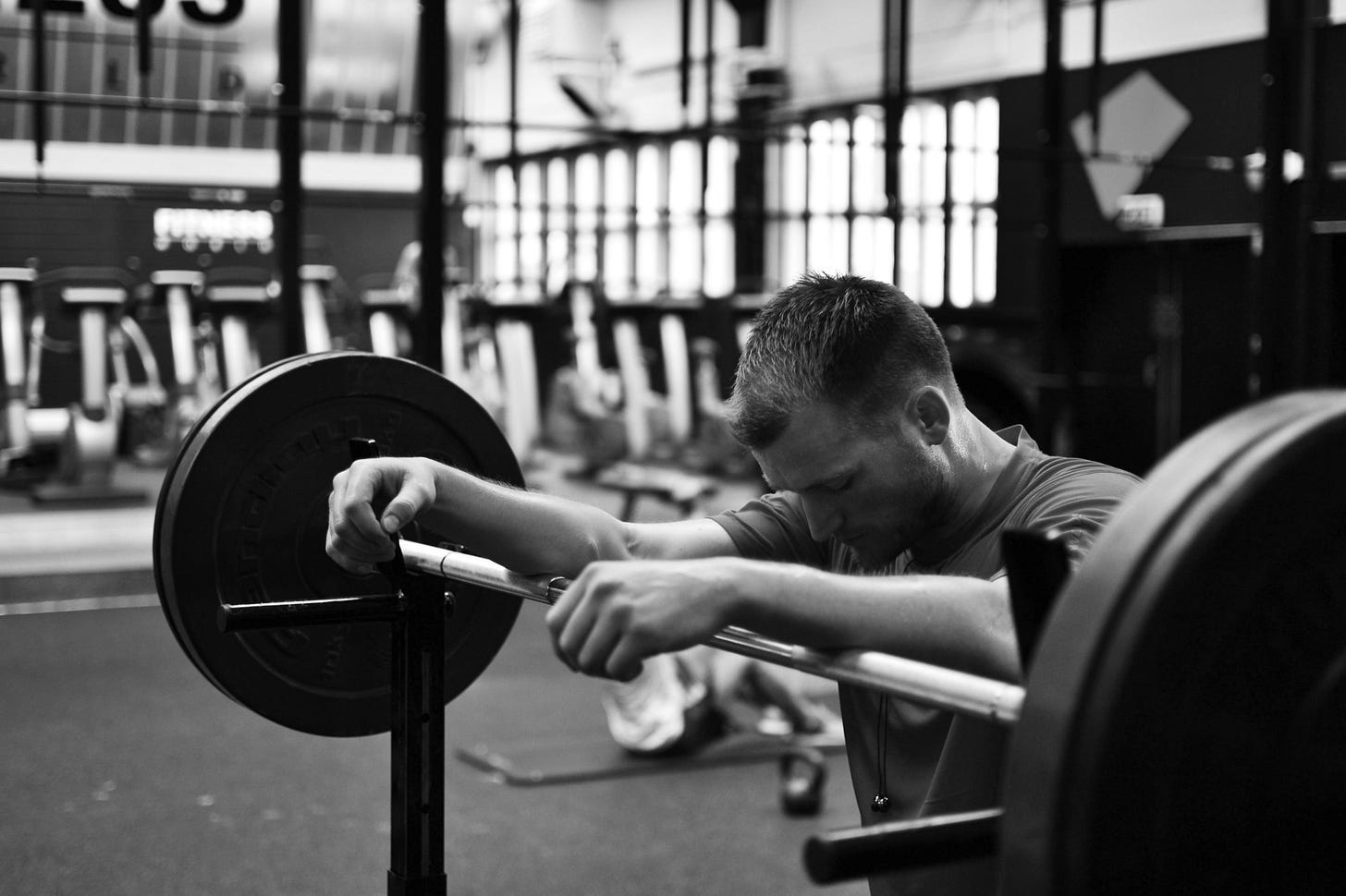 black and white image of a guy leaning on a weights rack for article by Larry G. Maguire