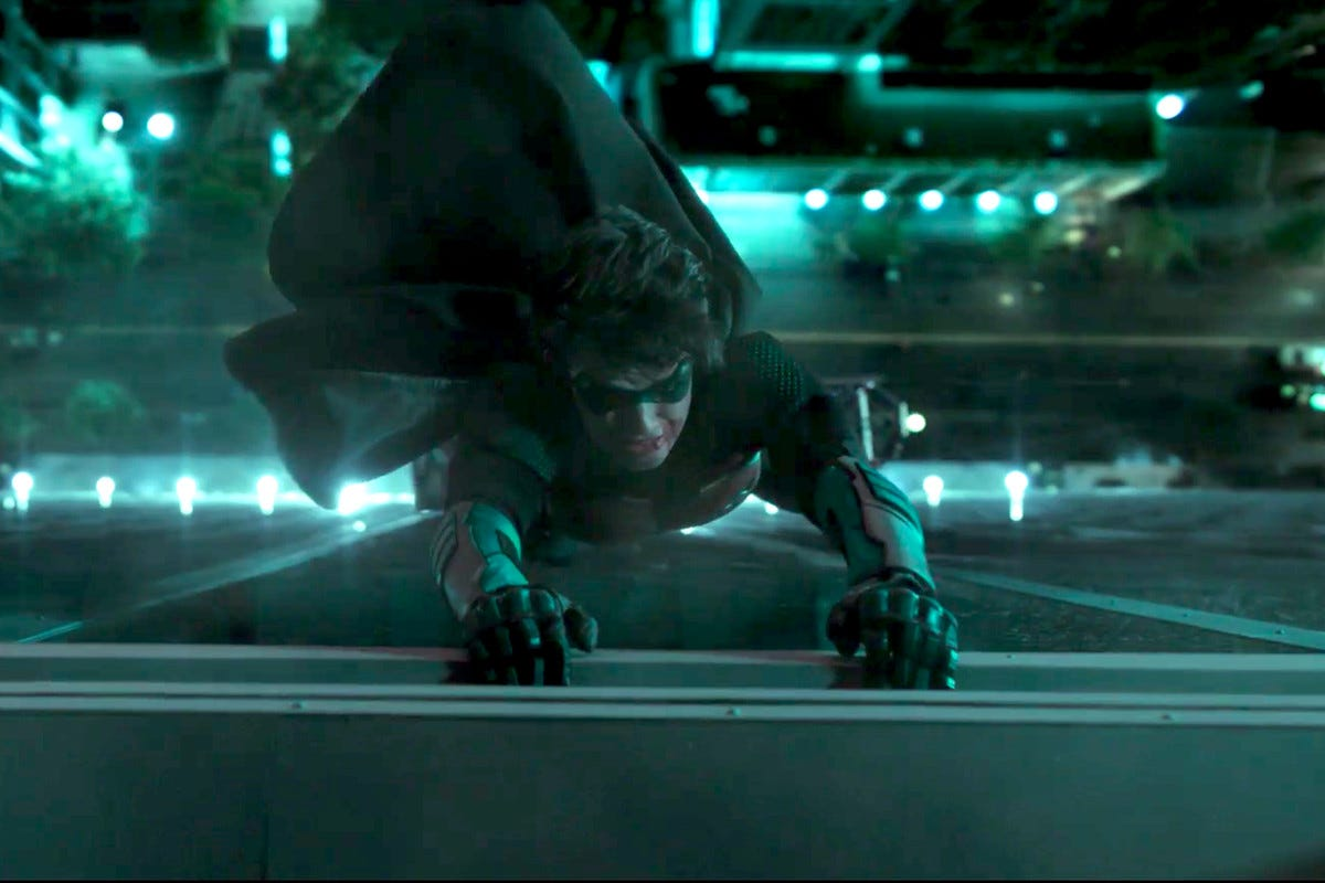 Jason Todd (Curran Walters) hangs by his hands from the edifice of a building, in Titans.