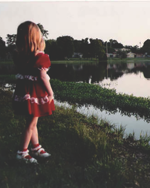 a young girl-child with shoulder-length blonde hair wearing a red dress stands in swampy area, looking at a body of water