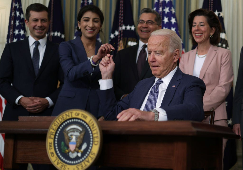 """President Joe Biden passes a signing pen to Federal Trade Commission Chairwoman Lina Khan during the signing of an executive order Friday on """"promoting competition in the American economy."""""""