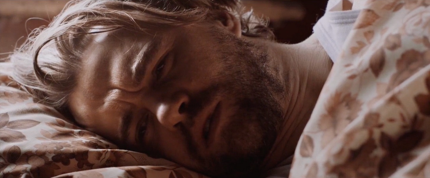 A closeup of a man lying in bed, light coming in from the window we can't see above his head. He looks very concerned and upset as he wakes from a dream