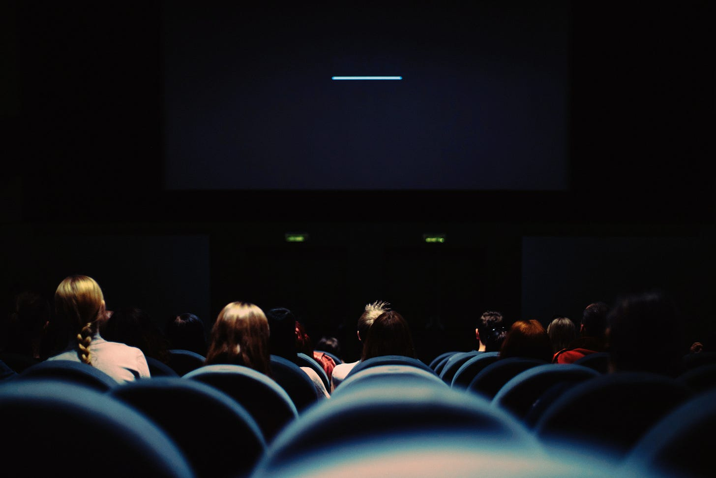 Behind a crowd of people. seated in a dark movie theater.