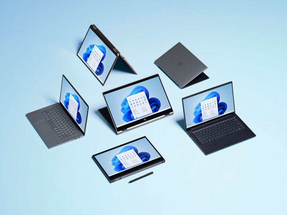 Windows 11 shown on a group of laptops. (Microsoft)