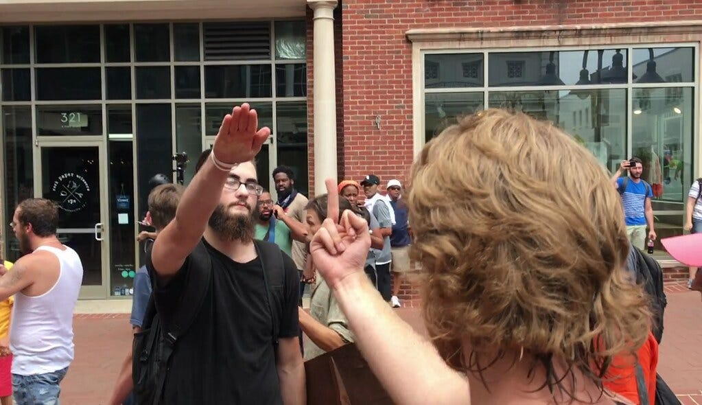 A counter-protester gives a white supremacist the middle finger. The white supremacists responds with a Nazi salute.