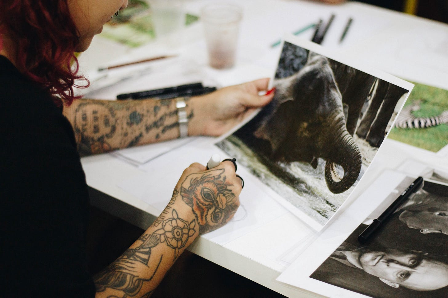 Tattooed lady looking at an elephant photograph for article by Larry G. Maguire