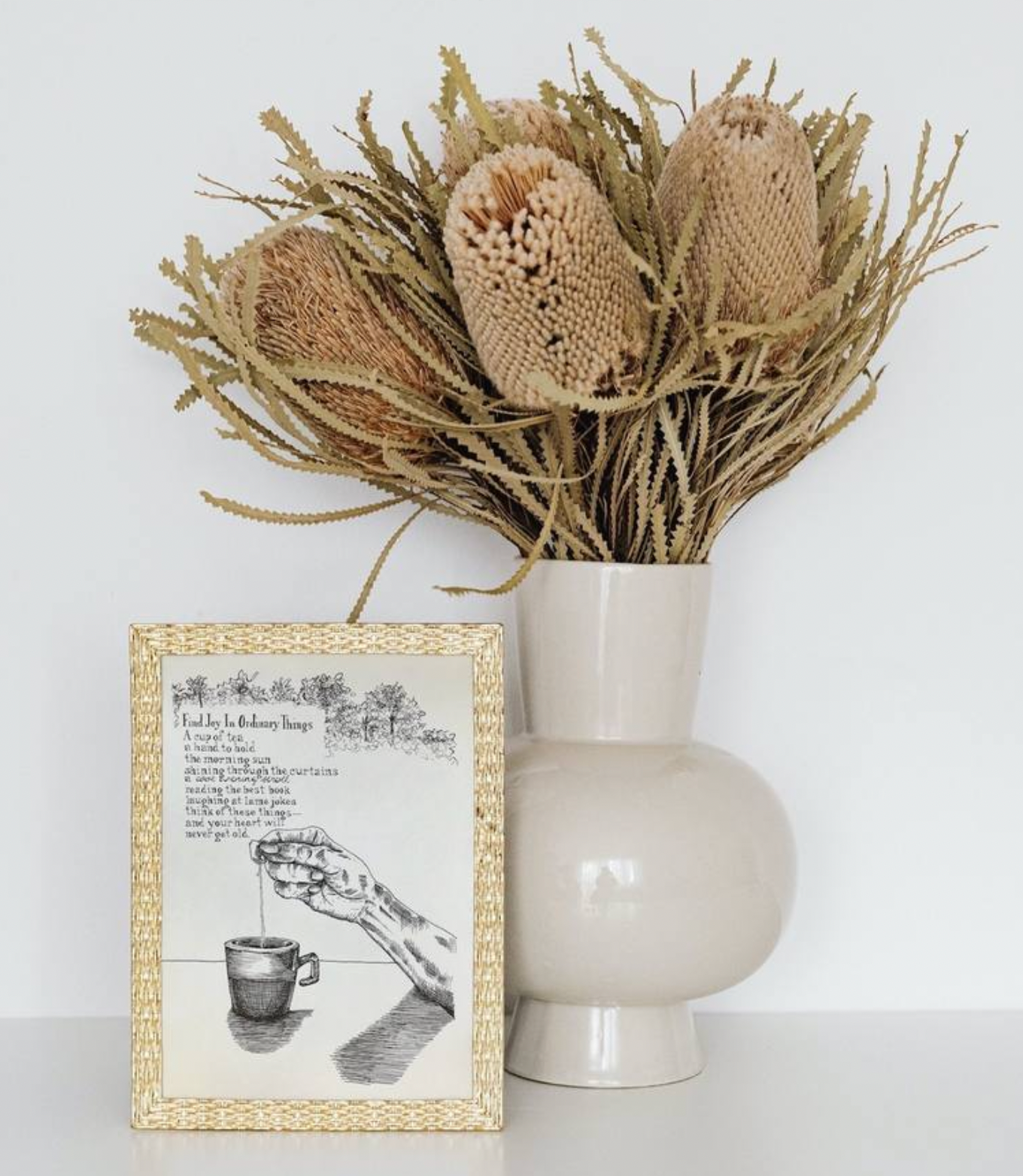 A photo of the mock-up of the artwork, Find Joy In Ordinary Things Illustrated Poem in a muted gold, weaved frame, beside it is a light beige coloured vase with dried flowers in autumn colours of golden yellow, light brown, and cream.