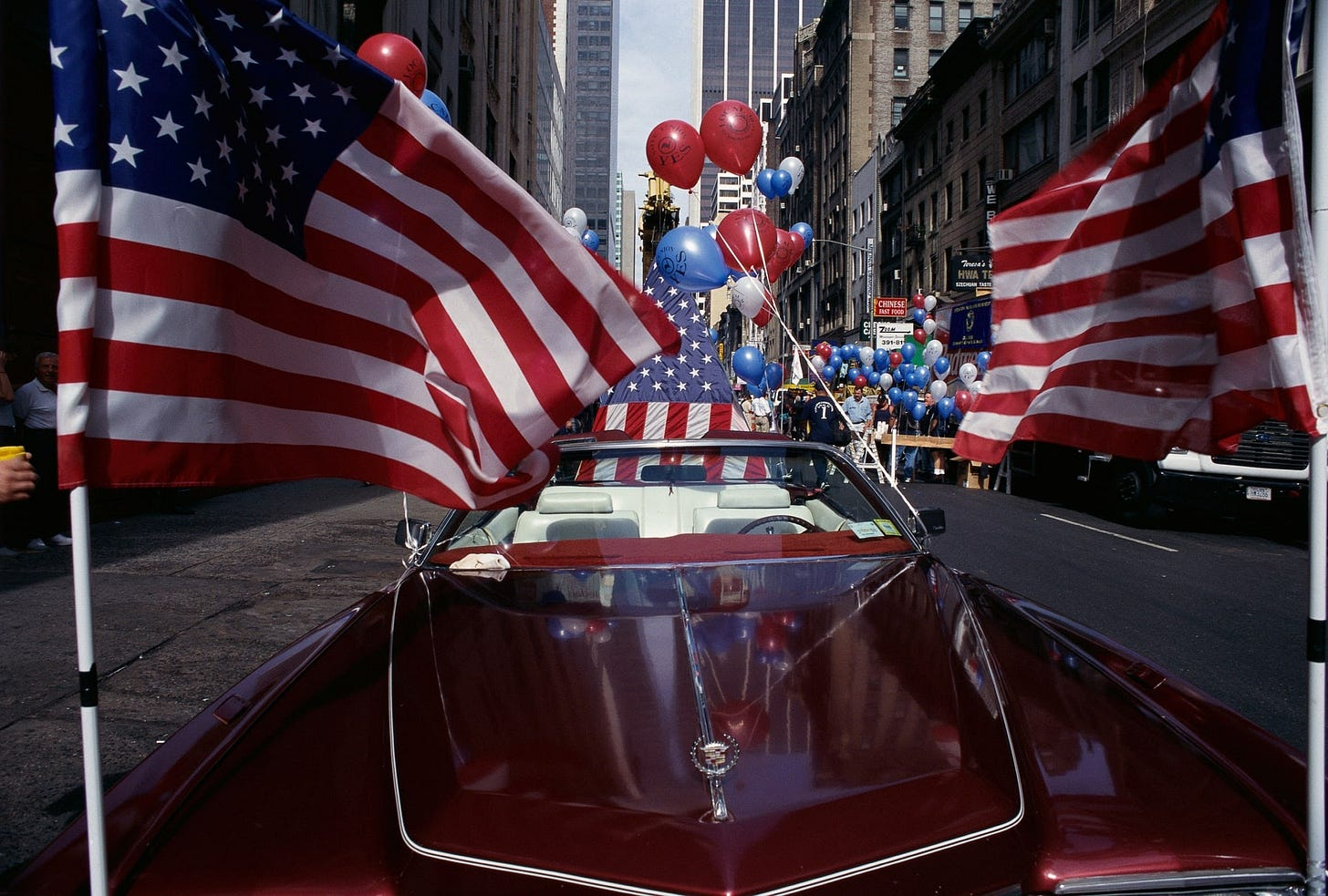 red white and blue balloons and many american flags attached to a red cadillac on the streets of new york city