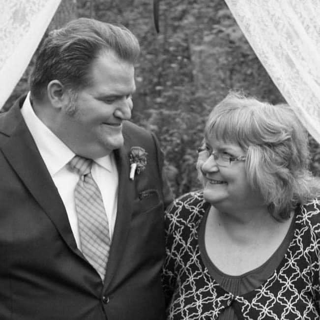 The author and his mother smiling at each other at his wedding.