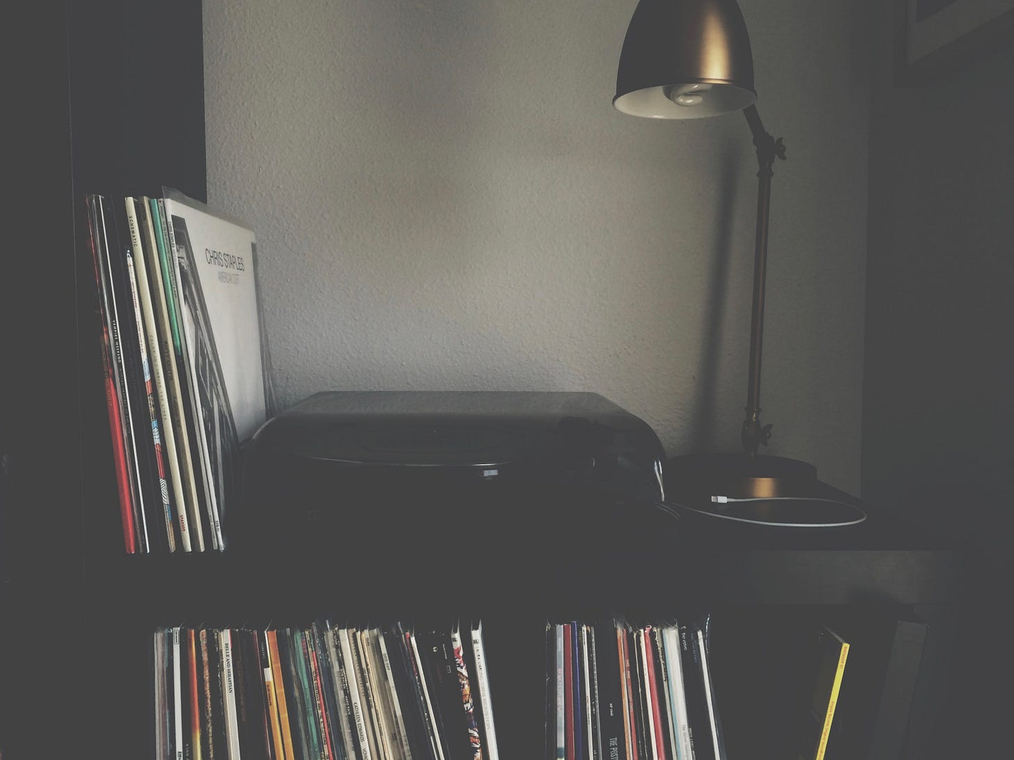 a record player with vertical stacks of records next to and on shelves underneath. An arm-style lap next to it.