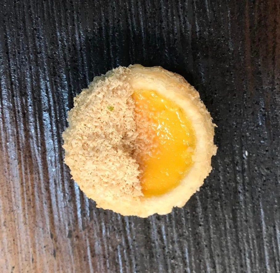 An overhead viewpoint of a egg custard tart on a dark slate background
