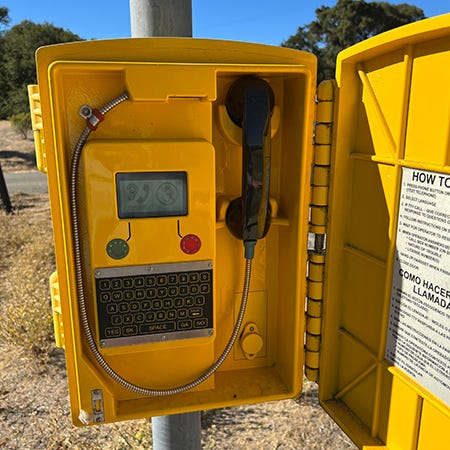 A picture of a California highway emergency call box, which is an open yellow case affixed to a pole with a black telephone receiver, a green button for audio, a red button for now audio, and a QWERTY keypad.