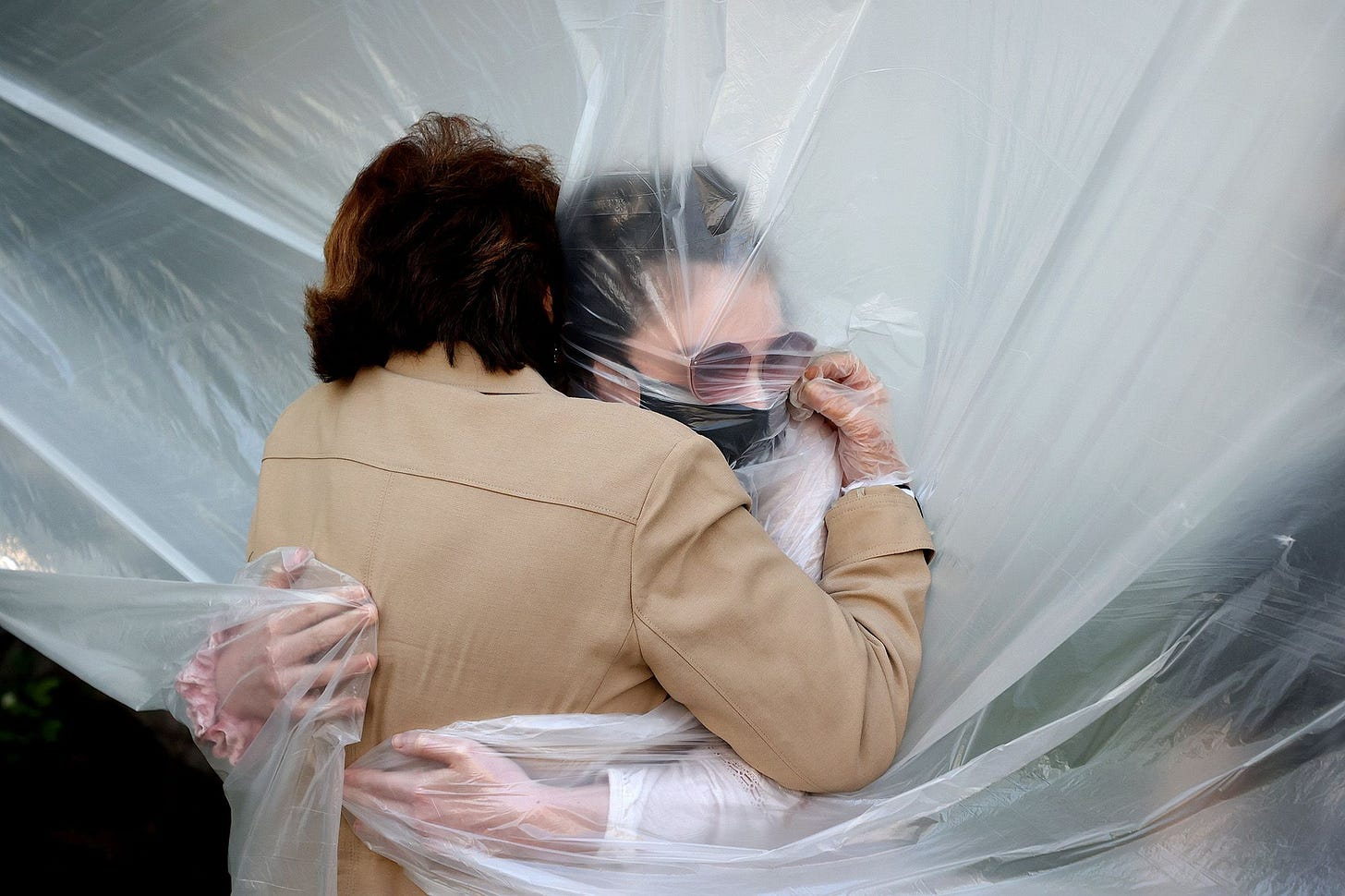 Olivia Grant, right, hugs her grandmother, Mary Grace Sileo, through a plastic drop cloth hung up on a homemade clothes line in Wantagh, N.Y.