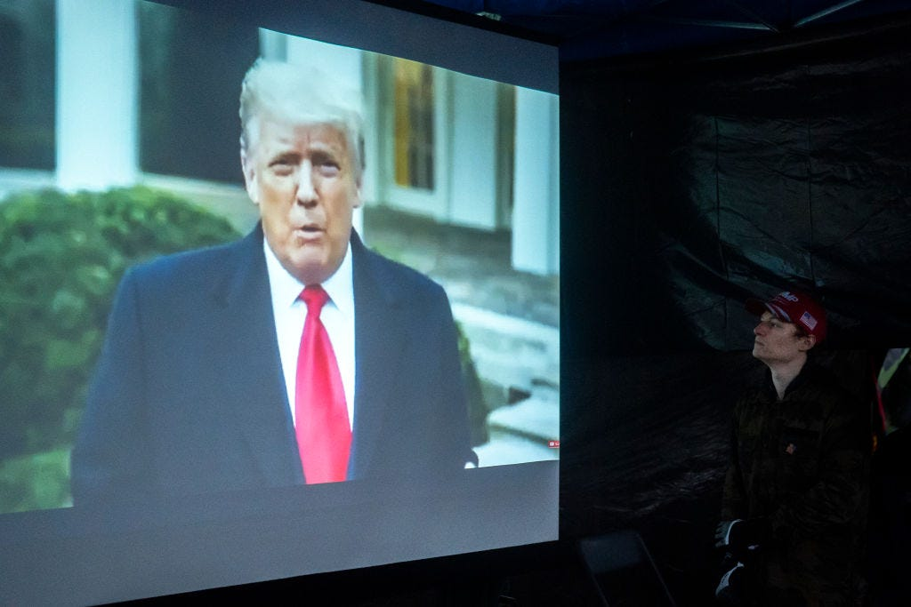 A supporter of President Trump watches a message asking violent protesters to go home on January 6, 2021 in Salem, Oregon. Trump supporters gathered at state capitals across the country to protest today's ratification of Joe Biden's Electoral College victory over President Trump in the 2020 election. (Photo by Nathan Howard/Getty Images)