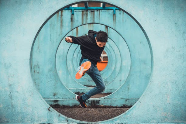 Young Asian active man in action of jumping and kicking, circle looping wall background. Extreme sport activity, parkour outdoor free running, or healthy lifestyle concept Young Asian active man in action of jumping and kicking, circle looping wall background. Extreme sport activity, parkour outdoor free running, or healthy lifestyle concept fearles stock pictures, royalty-free photos & images