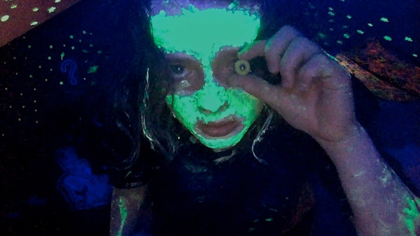 Character named Casey, covered in glowing face paint, stares into a webcam, holding a button to her eye.