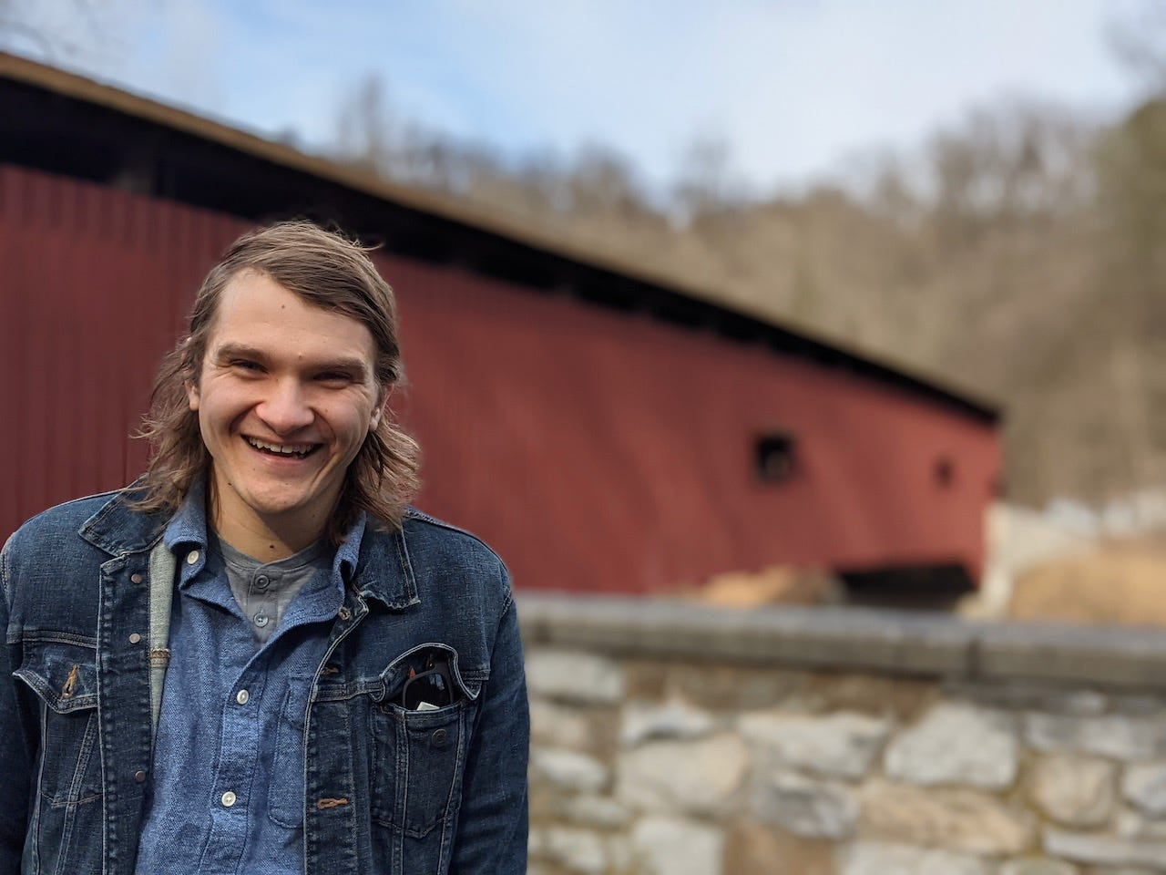 brett standing in front of a covered bridge