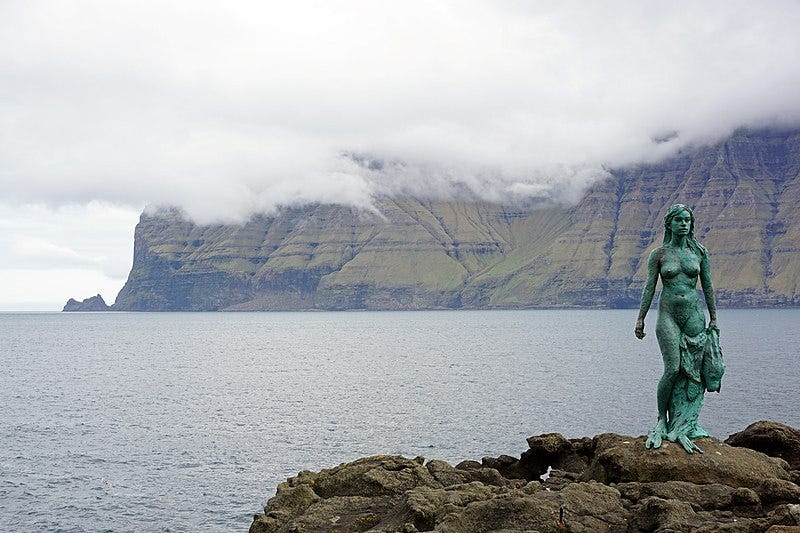 In the lower right corner, a bronze (bluey green) statue of a naked woman with long hair is holding a seal skin in her left hand. She is facing the camera and standing on a rock. In the background, thick white clouds hang over a green rocky land mass. The sea is between both of them.