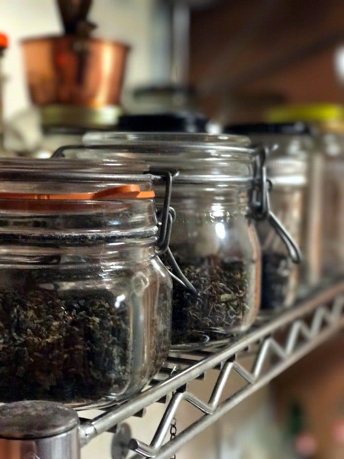 glass jars filled with looseleaf teas, sitting on a metal shelf