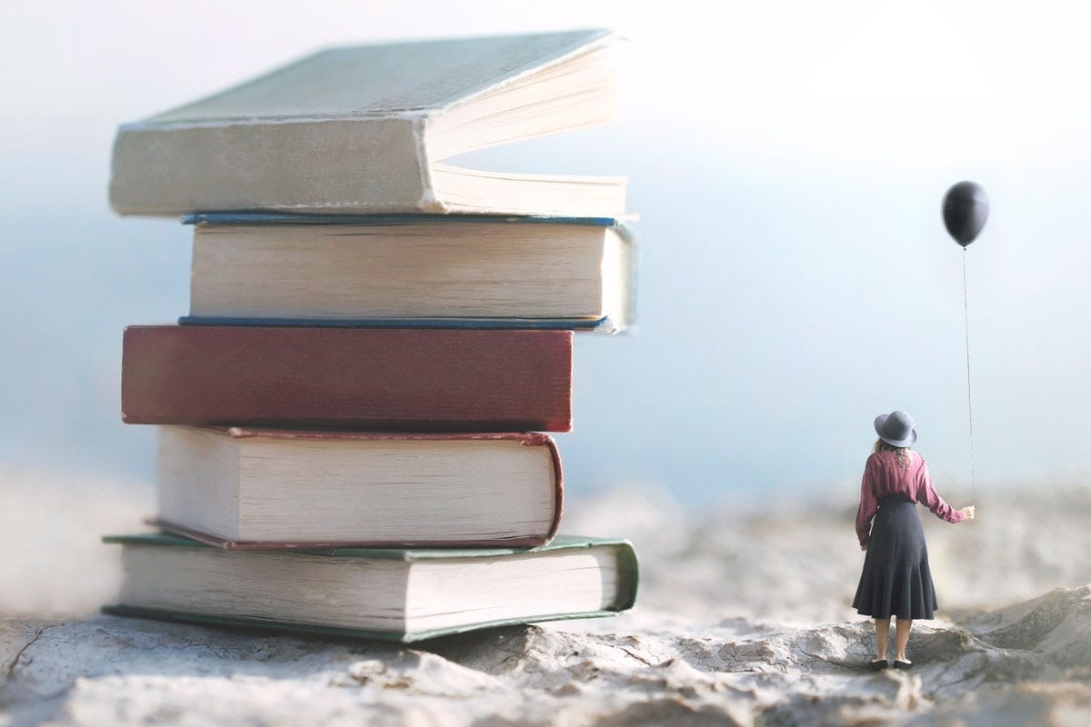 Woman Holding Balloon Standing Beside Giant Stack of Books on Beach